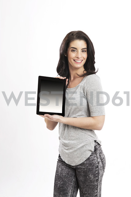 Portrait of smiling young woman showing digital tablet - GDF000686