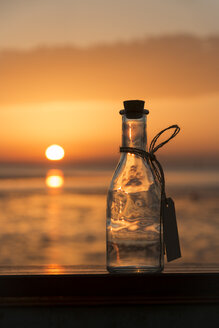 Germany, Lower Saxony, Wremen, Empty bottle at sunset - SJF000140