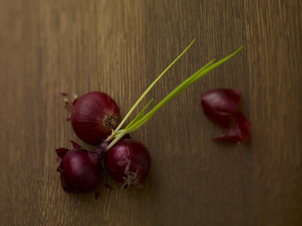 Four red onions on wood - SRSF000545