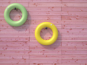Two floating tires hanging on pink wooden wall - UWF000377