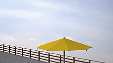 Yellow sunshade on wooden terrace in front of cloudy sky, 3D Rendering - UWF000374