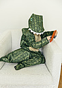 Little boy wearing dinosaur costume sitting on the couch with smartphone - MFF001482