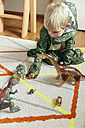 Little boy wearing dinosaur costume playing with toy dinosaurs - MFF001487