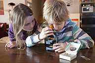 Brother and sister with microscope at home - SARF001359