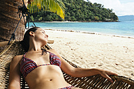 Philippines, Palawan, Woman relaxing on beach hammock - GEMF000048