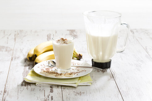 Glass of banana milkshake with whipped cream and chocolate granules - MAEF009728