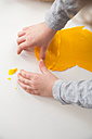 Little girl playing with yellow modeling clay - LVF002846
