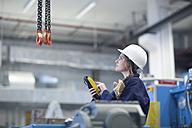 Technician in factory hall using regulator for hook - SGF001328