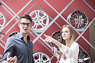 Shop assistant showing woman in tyre shop the selection of available rims - ZEF003991