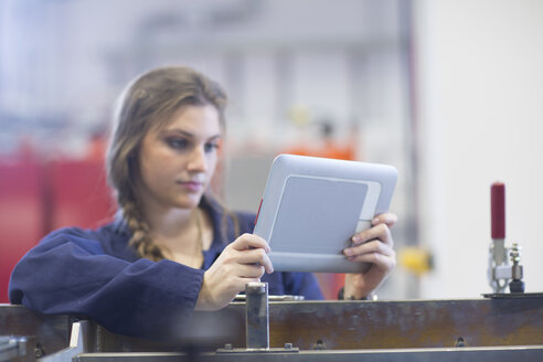 Technician in factory hall using digital tablet - SGF001341