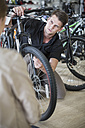 Young man working in bicycle shop - ZEF005029