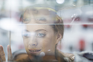 Young woman looking through shop window - ZEF005039
