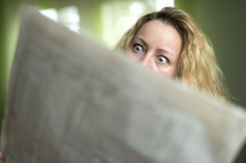 Horrified woman reading newspaper - FRF000199