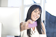 Portrait of smiling woman at desk holding post it - ZEF003700