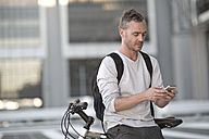 Blone man on bicycle using smart phone - ZEF004944