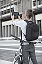 Man with rucksack and bike taking picture with digital tablet - ZEF004506