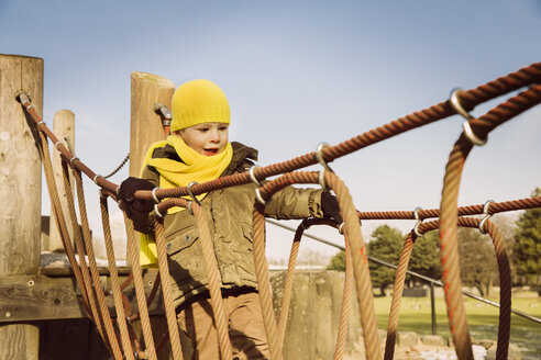 Little boy walking along a hanging bridge on a playground - MFF001501