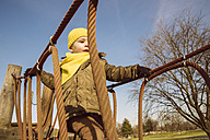 Little boy walking along a hanging bridge on a playground - MFF001504