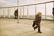 Germany, Cologne, happy little boy running on the roof of a high-rise building - MF001505