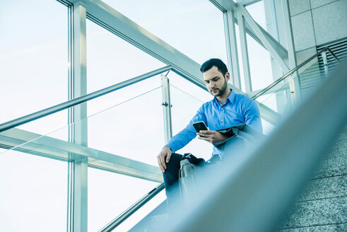 Young businessman sitting on stairs looking on cell phone - UUF003456