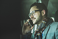 Young businessman talking on cell phone in car - UUF003439