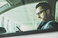 Young businessman in car looking at digital tablet - UUF003441