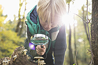 Little boy watching mushrooms with magnifying glass in a forest - PDF000810