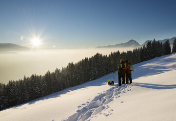 Austria, Tyrol, Schwaz, couple with snowshoes looking at view - MKFF000171