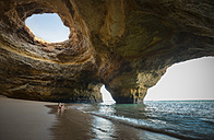Portugal, beach of Benagil, cave, woman sitting at seafront - STCF000087