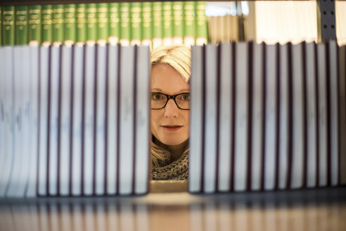Woman in library looking from behind bookshelf - CHP000106