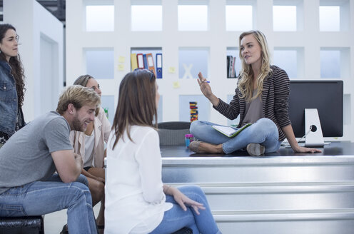 Creative office woman sitting on her desk and meeting with her colleagues - ZEF003021