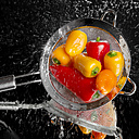 Mini peppers in a colander being washed on a mirror face - CSTF000866