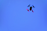Flying miniature drone in front of blue sky - HOHF001270