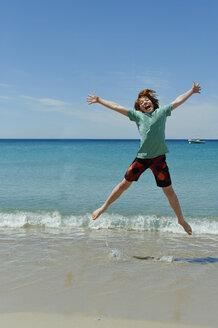 France, Corsica, Favone, boy having fun at a beach - LBF001065