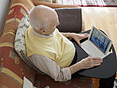Grandfather videoconferencing with grandchildren via digital tablet - LAF001330