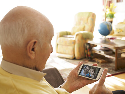 Grandfather videoconferencing with grandchildren via smartphone - LAF001332
