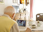 Grandfather videoconferencing with grandchildren via digital tablet - LAF001334