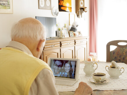 Grandfather videoconferencing with grandchildren via digital tablet - LAF001334