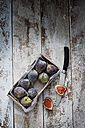 Cardboard box of figs and knife on wood - CSF024599
