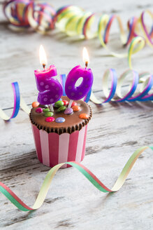 Birthday muffin with chocolate buttons and lighted candles - SARF001415