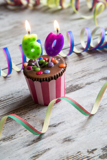 Birthday muffin with chocolate buttons and lighted candles - SARF001419