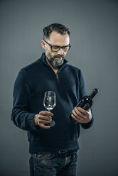 Man with red wine glass and wine bottle - IPF000189