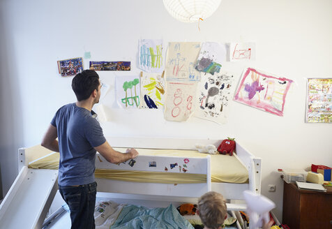 Father and son in kid's room, looking at children's drawings - RH000551