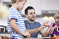 Father tinkering in kitchen with son and daughter - RHF000560