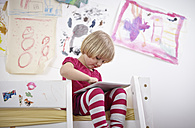 Little girl sitting on bunk bed, drawing on touch pad - RHF000589