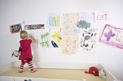 Little girl painting on wall of children's room, rear view - RHF000597