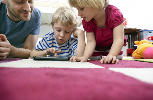 Father and children using mini tablet, lying on floor - RHF000603