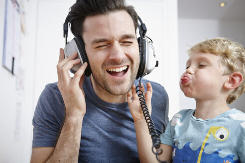 Father and son listening to music with headphones - RHF000633