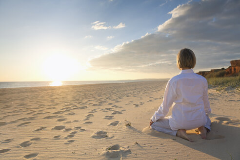 Portugal, Algarve, woman doing yoga exercises at beach house at sunset - MSF004494