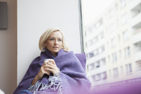 Portrait of woman with cup and woolen blanket looking through window - RBF002454